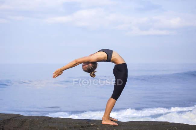 Индонезия, Бали, женщина, практикующая йогу на побережье — стоковое фото