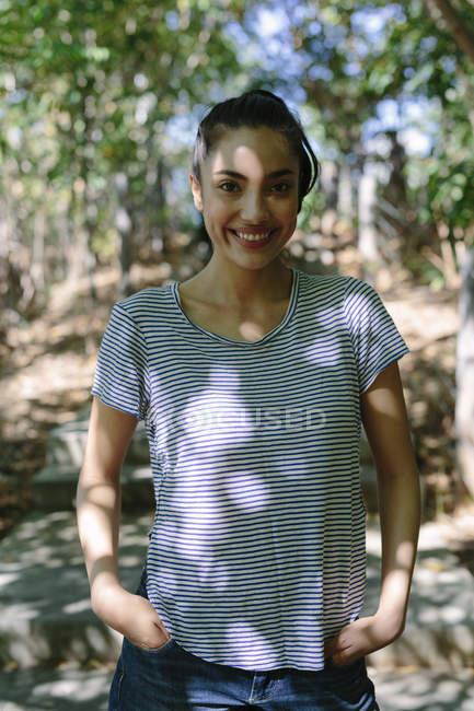 Портрет посміхаючись молода жінка з руки в кишені — стокове фото