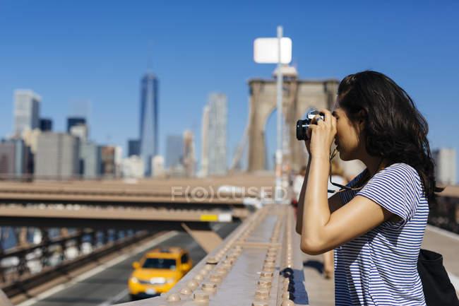 USA, New York, giovane donna in piedi sul ponte di Brooklyn che scatta una foto con la macchina fotografica — Foto stock