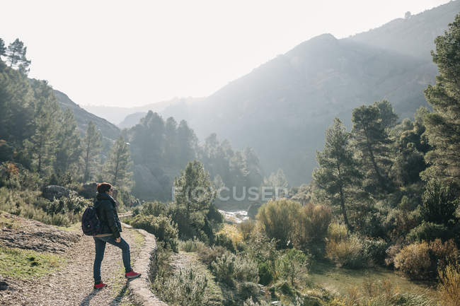 Spain, Catalonia, Parc Natural dels Ports, woman with backpack standing on hiking trail — Stock Photo