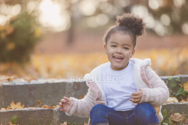 Girl sitting on steps in autumn park — Stock Photo