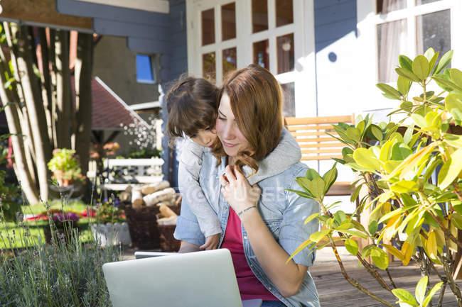 Mãe e filha usando laptop no terraço do jardim — Fotografia de Stock