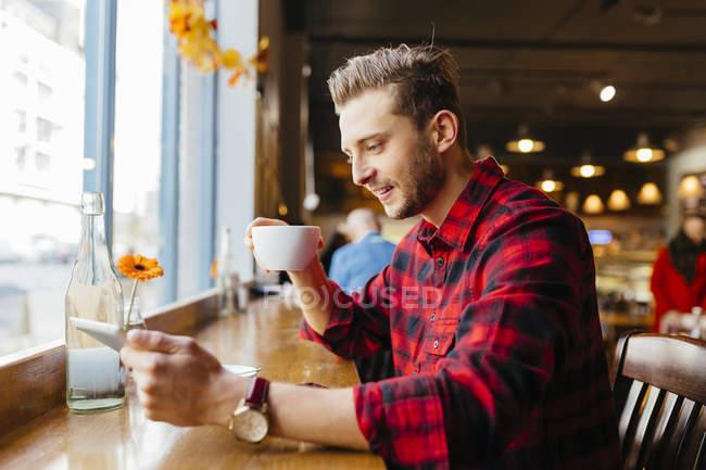 Людина в кафе, дивлячись на цифровий планшетний — стокове фото