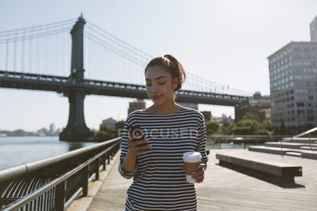 USA, New York, ritratto di una giovane donna sorridente con il caffè per andare a guardare il suo smartphone — Foto stock