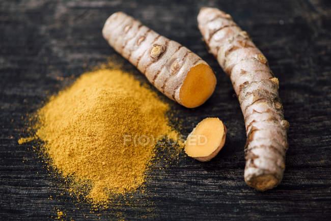 Nahaufnahme von frischen Kurkuma und Pulver auf schwarzer Holztisch — Stockfoto