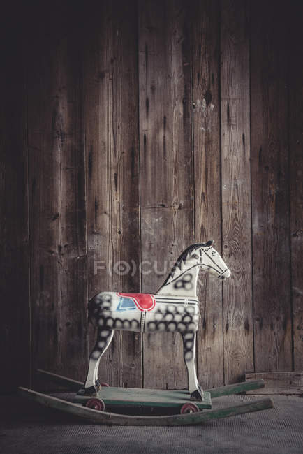 Vintage rocking horse in a barn in front of a wooden wall — Stock Photo