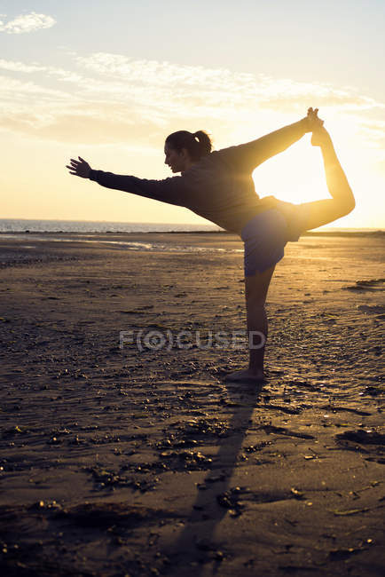 Spain, Puerto Real, silhouette of young woman doing yoga on the beach at sunset — Stock Photo