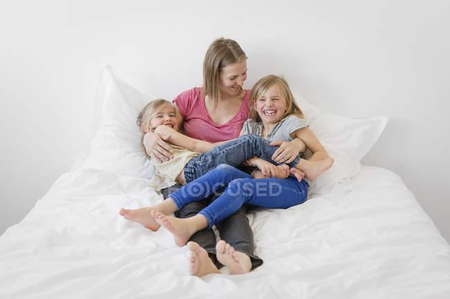 Madre con sus hijas pequeñas risas en la cama - foto de stock