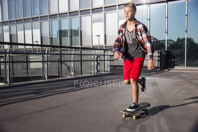Caucasian teenager boy riding on skateboard outdoor — Stock Photo