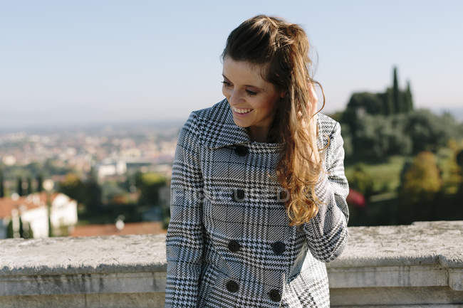 Smiling brunette woman in checkered coat — Stock Photo