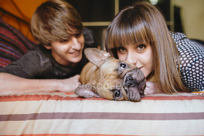 Young couple lying on the bed with their French bulldog — Stock Photo