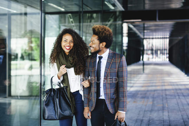 Two smiling young business people walking outdoors — Stock Photo