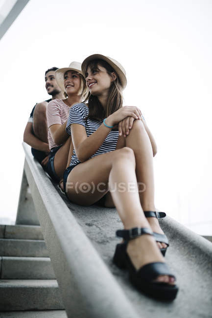 Friends sitting together and looking sideways — Stock Photo