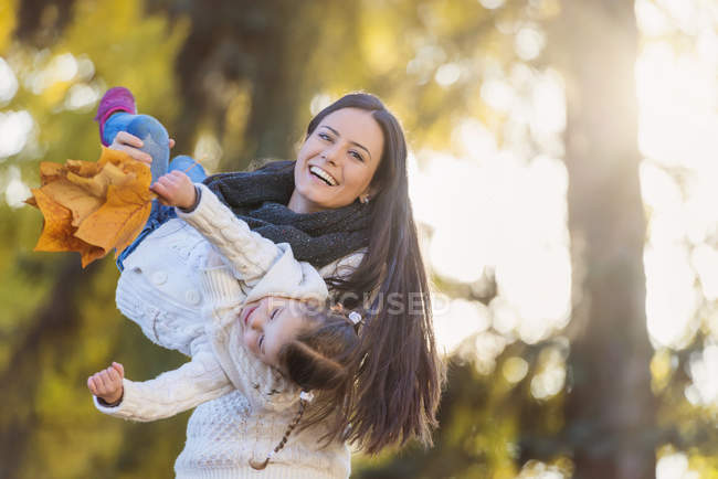 Happy mother carrying daughter holding autumn leaves — Stock Photo