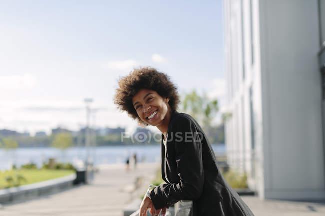 Портрет улыбающейся деловой женщины, опирающейся на перила — стоковое фото