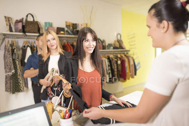 Young women shopping for clothes in fashion boutique — Stock Photo