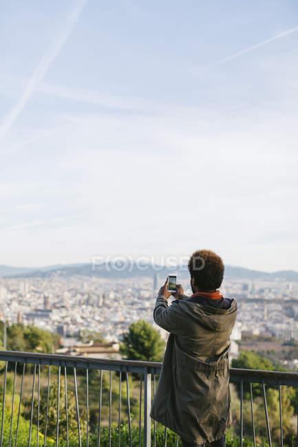Volta a vista da jovem tirando uma foto de exibição com seu smartphone — Fotografia de Stock
