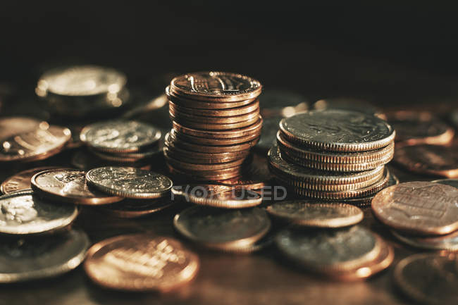 Heap and stacks of coins on wooden surface — Stock Photo