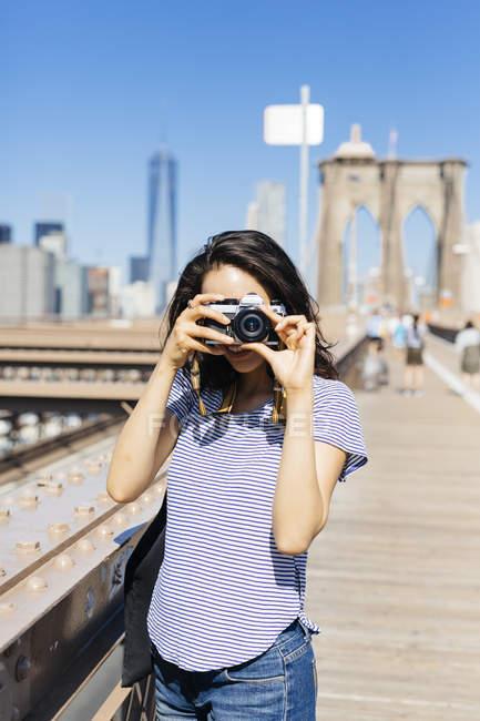 EUA, Nova York, jovem mulher de pé na Ponte Brooklyn tirando uma foto com câmera — Fotografia de Stock