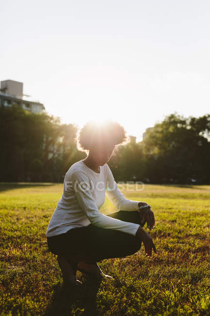 Young woman crouching on a meadow at backlight — Stock Photo