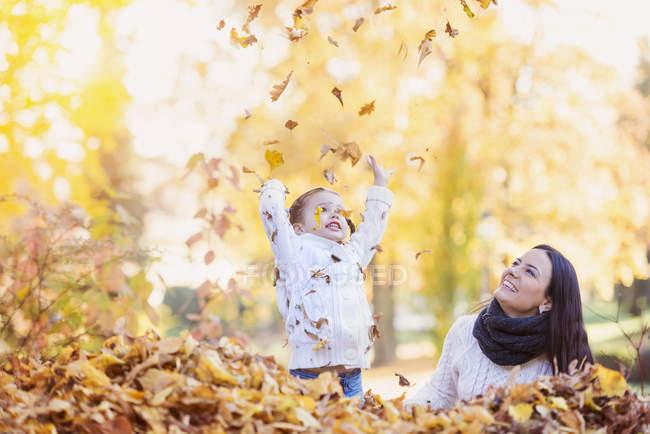 Glückliches Mädchen mit Mutter, die mit Herbstblättern spielt — Stockfoto