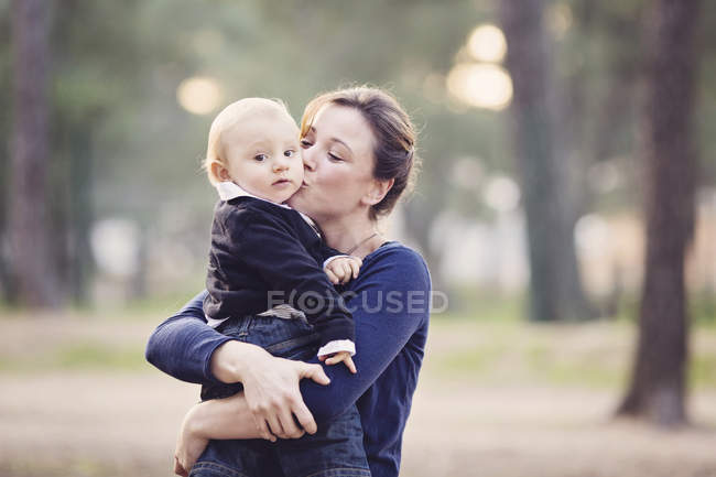 Mother holding baby boy in her arms and kissing him on the cheek — Stock Photo