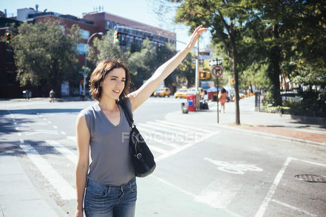 Young woman hailing a taxi — Stock Photo