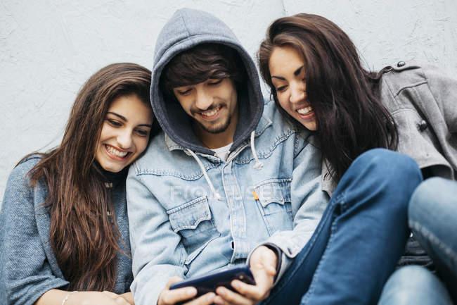 Três amigos compartilhando o celular ao ar livre — Fotografia de Stock