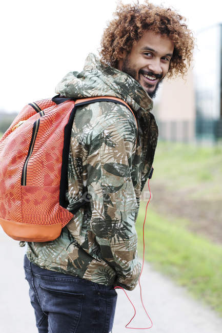 Portrait of man with dyed ringlets wearing camouflage jacket and backpack looking over his shoulder — Stock Photo