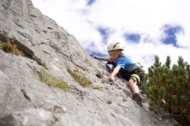 Menino pequeno escalando a rocha — Fotografia de Stock