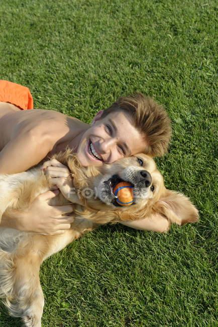 Adolescent jouant avec Golden Retriever sur pelouse — Photo de stock