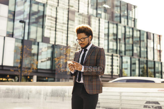 Young businessman outdoors looking at cell phone — Stock Photo
