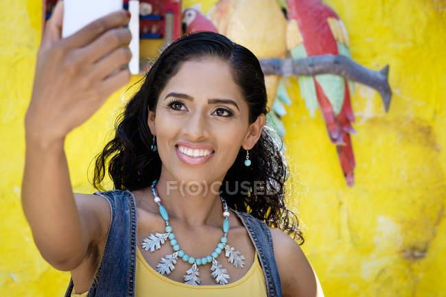 Portrait de femme souriante prenant un selfie avec smartphone — Photo de stock
