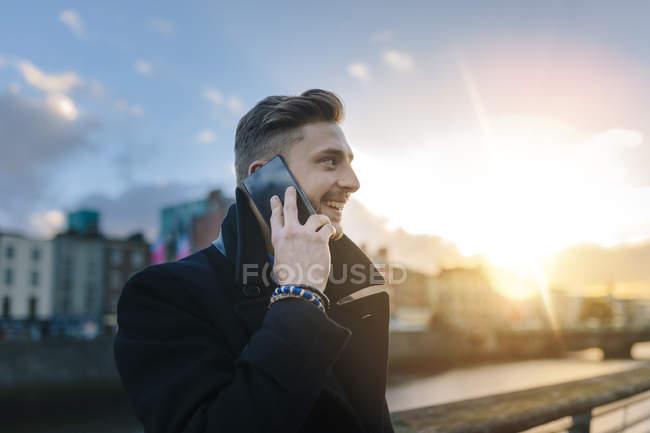 Irlanda, Dublino, giovane uomo d'affari sorridente che telefona con lo smartphone alla retroilluminazione — Foto stock