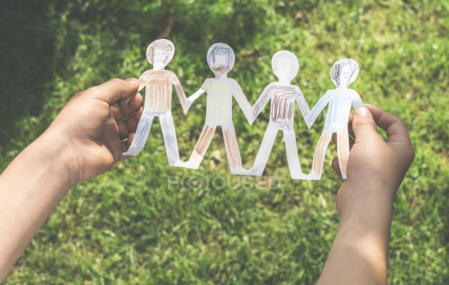 Cortada a exibição das mãos de criança segurando uma cadeia de figuras de papel pintado na frente de um prado — Fotografia de Stock