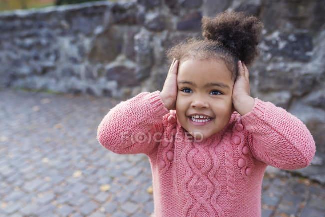 Menina sorridente segurando as mãos sobre as orelhas — Fotografia de Stock