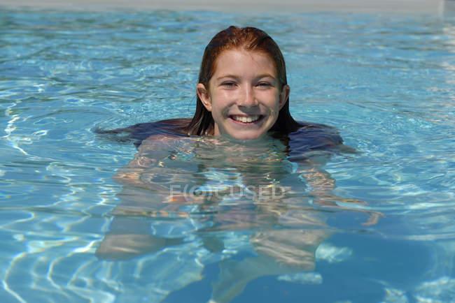 Retrato de menina sorridente na piscina — Fotografia de Stock