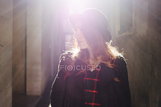Young woman in the city in back light — Stock Photo