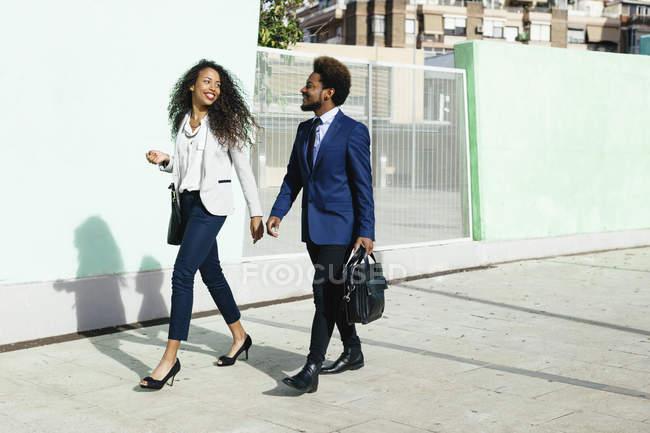 Giovane coppia sorridente indossando affari abbigliamento camminare mano nella mano sul marciapiede — Foto stock