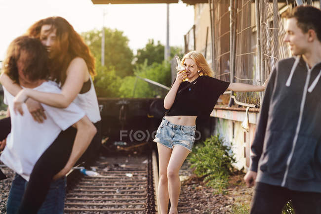 Four friends fooling around on rail — Stock Photo