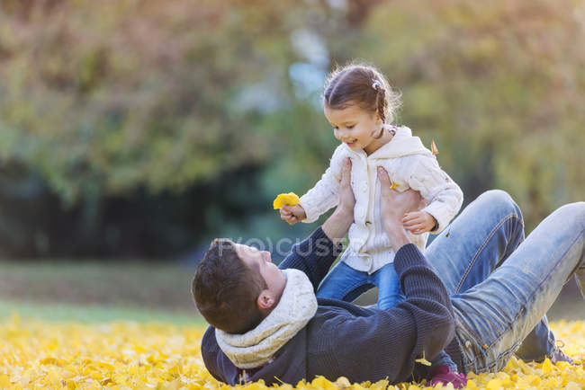 Happy father with daughter in autumn leaves — Stock Photo