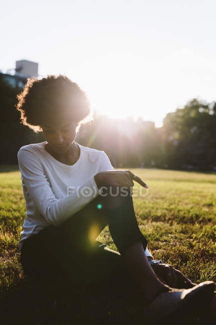 Young woman sitting on a meadow at backlight — Stock Photo