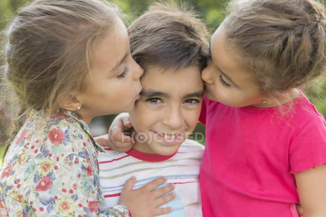 Два маленьких дівчаток цілуватися хлопчик на відкритому повітрі — стокове фото