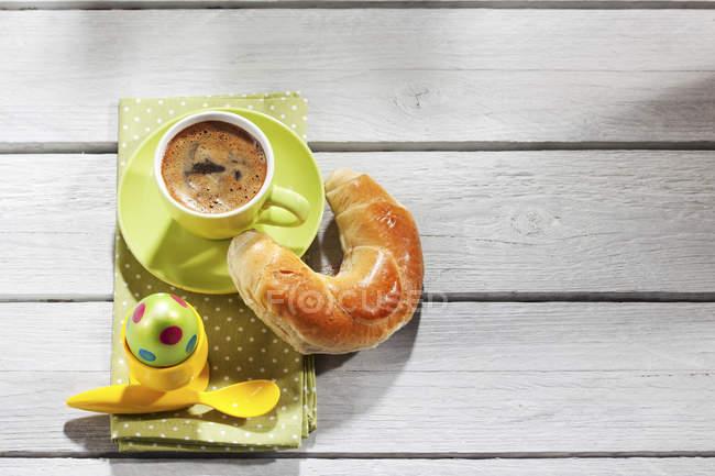 Завтрак с Окрашенные пасхальное яйцо, чашку кофе и кондитерские изделия — стоковое фото