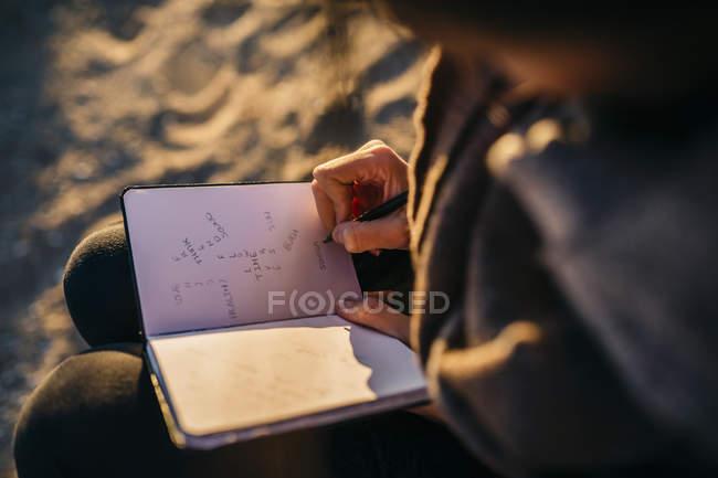 Frau schreibt am Strand in Notizbuch — Stockfoto