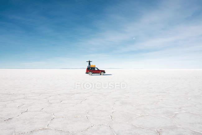 Atacama, Altiplano, Bolivia, Salar de Uyuni, hombre que está parado en la azotea del coche en el desierto - foto de stock