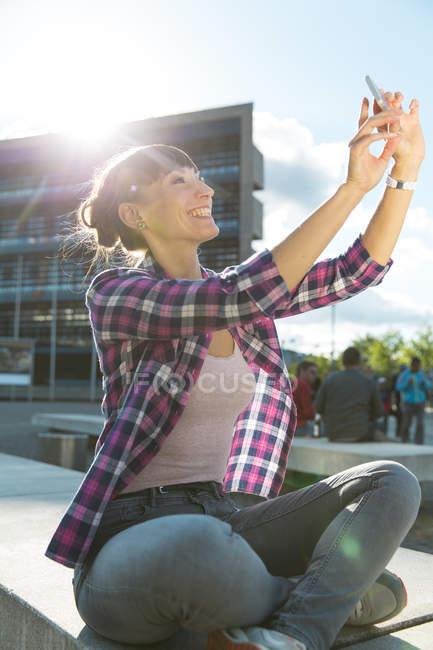 Портрет счастливой молодой женщины, делающей селфи со смартфоном — стоковое фото