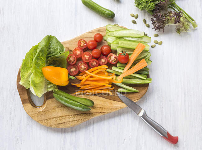 Chopped fresh vegetables on wooden chopping board — Stock Photo