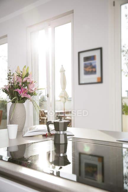 Blumenstrauß und Kaffeemaschine auf Ofen im Küchenblock — Stockfoto