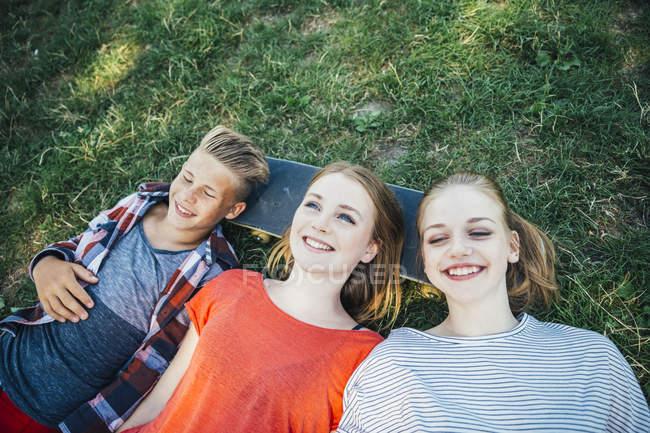 Three happy teenage friends lying on skateboard in meadow — Stock Photo